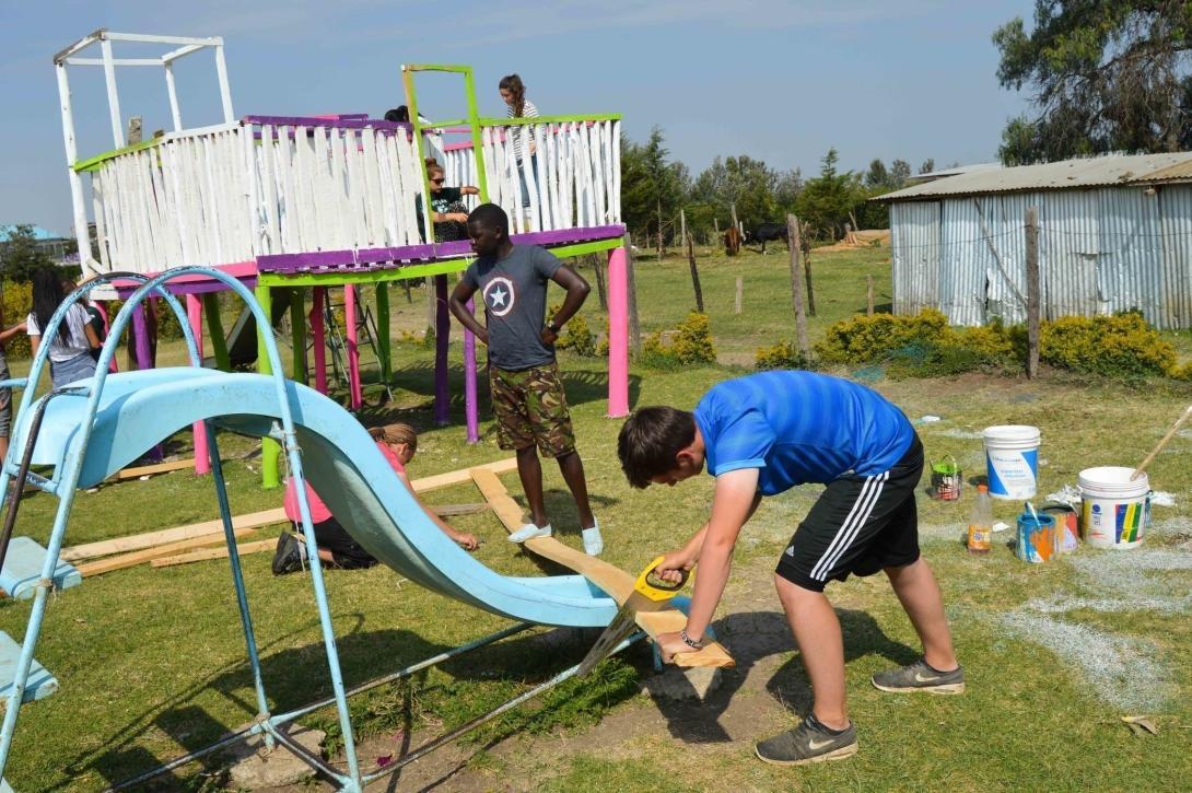 Volontärer bygger en lekplats under handledning av Projects Abroad personal under en volontärresa.
